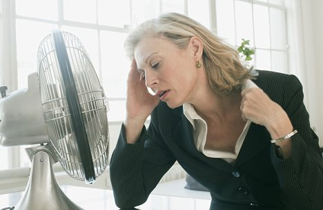Hot businesswoman sitting in front of fan --- Image by © Sean De Burca/Corbis